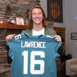 Trevor Lawrence holds up his jaguars jersey for the cameras